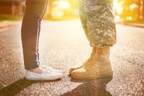 Street view of lower legs & feet of military service member in uniform and his girl